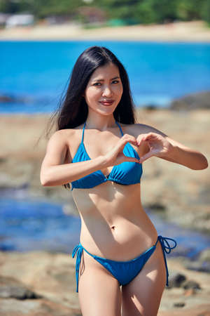 Photo pour Beautiful asian woman showing heart - love's symbol and smile on the beach with rocks in a blue bikini - image libre de droit