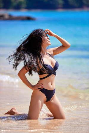 Photo pour Beautiful asian woman enjoying on a tropical beach in a black swimsuit - image libre de droit