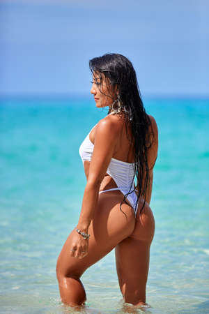 Photo pour Sexy girl in white swimsuit posing at the tropical beach in Thailand - image libre de droit