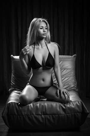 Photo pour Sexy asian girl model in fancy black bikini is posing on the sofa - image libre de droit