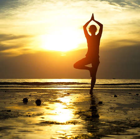Silhouette of a beautiful yoga woman in the evening