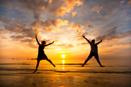 Photo pour Young couple in a jump on the sea beach at sunset - image libre de droit