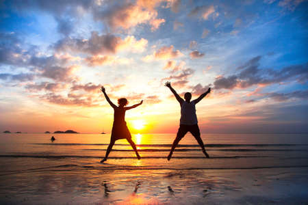 Photo pour Young couple in a jump on the sea beach at sunset  concept of long-awaited vacation  - image libre de droit