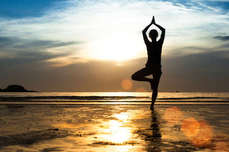Foto de Silhouette of a young woman practicing yoga on the beach at sunset   - Imagen libre de derechos
