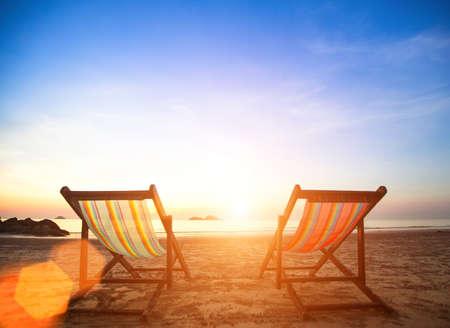 Couple of beach chairs on sea coast.