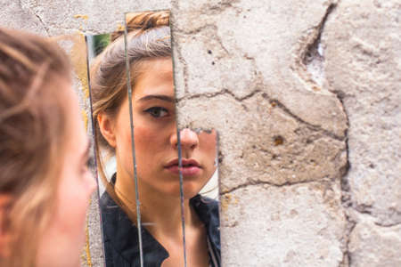 Photo pour Teen girl looking at her reflection in the mirror fragments on the wall at street. - image libre de droit