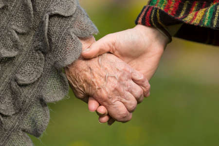 Photo for Holding hands together - old and young, close-up outdoors. - Royalty Free Image