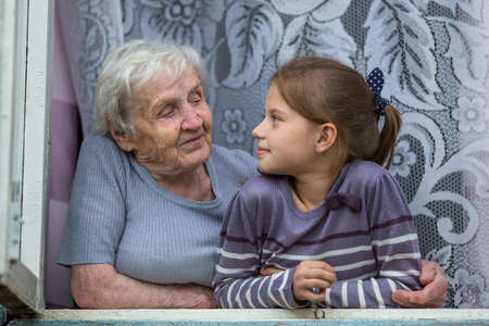 Photo pour Grandmother with little granddaughter sitting in the window. - image libre de droit