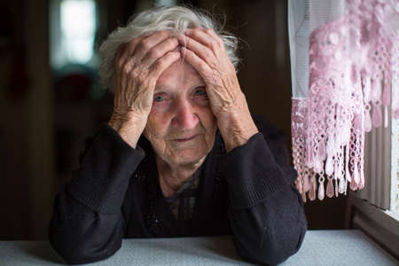 An elderly woman sitting at the table in sadness.