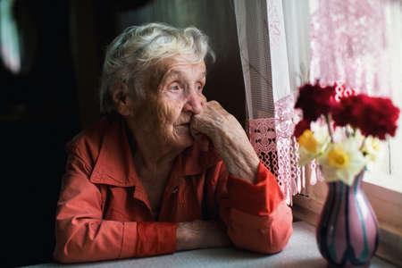 Foto de Elderly woman looks sadly out the window. - Imagen libre de derechos