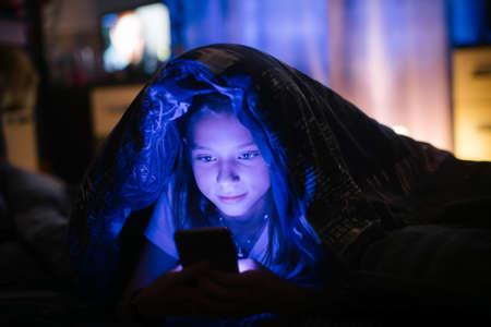 Foto de Little girl in bed under a blanket looking at the smartphone at night. - Imagen libre de derechos