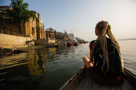 Photo for Woman traveler on a boat glides through the water on Ganges river along the shore of Varanasi, India. - Royalty Free Image