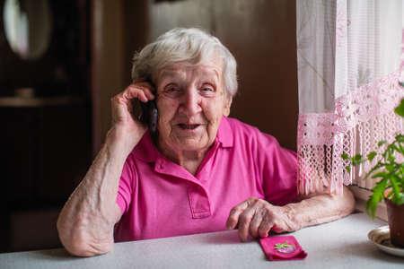 Foto de Elderly senior woman talks on a mobile phone. - Imagen libre de derechos