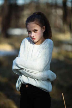 Photo pour Cute twelve year old girl in the park posing for the camera. - image libre de droit