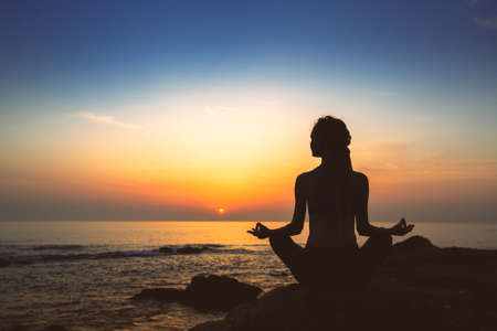 Photo pour Silhouette of woman yoga in Lotus position on the shore of ocean at evening. - image libre de droit