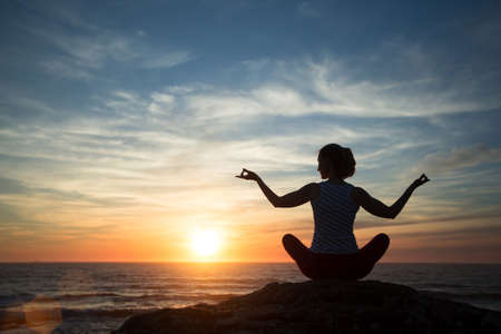 Photo pour Silhouette young woman practicing yoga on the beach at sunset. - image libre de droit