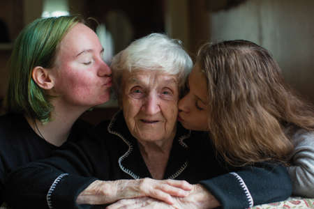 Photo pour Two girls granddaughter kissing her grandmother. - image libre de droit