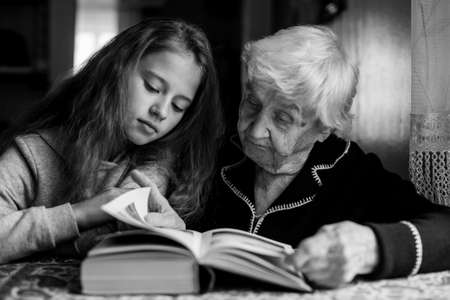 Photo pour Child of eleven with his grandmother together reading a book. Black and white photo. - image libre de droit