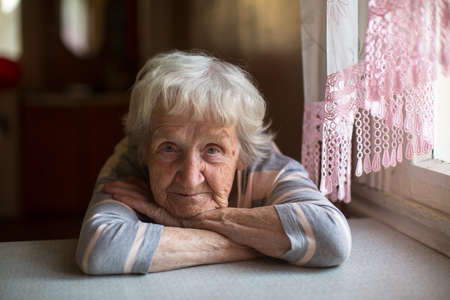 Photo pour Close-up portrait of a old woman at the table in home. - image libre de droit