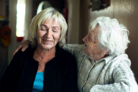 Portrait of a mature woman fooling with her old mother.
