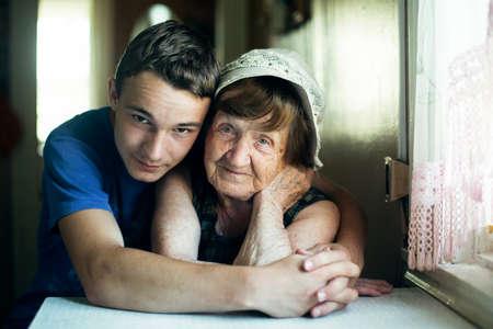 Photo pour An old woman and her grandson portrait together in an embrace. - image libre de droit