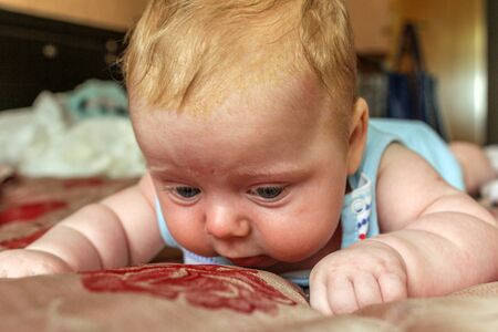 Photo pour newborn boy lies on his stomach on the bed and looking down. baby boy in the early days of home. - image libre de droit