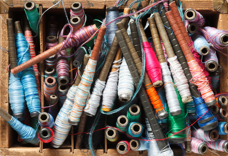 Colorful spools with threads for loom background.