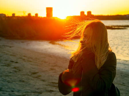 Photo for Silhouette of a lonely woman watching sunset in autumn. downtown buildings silhouettes. Nature Orange sea sunset in the city landscape beautiful landscape of Tallinn skyline Panoramic view on beach - Royalty Free Image