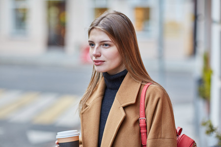 Photo pour Young stylish woman drinking coffee to go in a city street. - image libre de droit