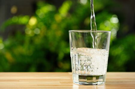 Photo pour pouring clear water in transparent glass in green garden - image libre de droit