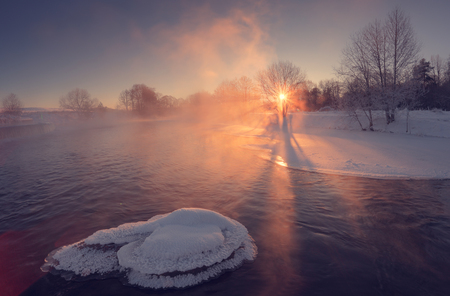 Sunny winter morning. Winter landscape with sun beams. Morning sun shine on snow. Winter background with bright sunrays.