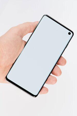 Foto de Modern smartphone in hand palm isolated on white studio background - Imagen libre de derechos