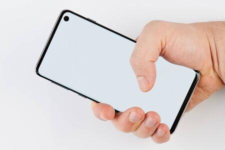 Foto de Hand hold modern smartphone isolated on white background - Imagen libre de derechos