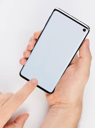 Foto de Using smartphone isolated. Modern phone in hand close up view - Imagen libre de derechos