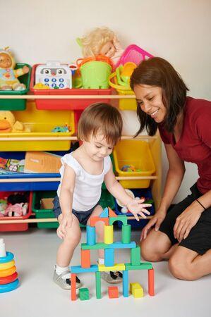 Photo pour Building castle baby activity. Nurse play with kid in daycare - image libre de droit