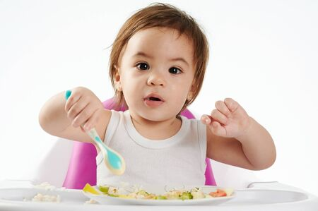 Photo pour Cute baby eating healthy food on high chair isolated - image libre de droit