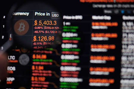 Photo pour New-York , USA - March 13, 2020: Bitcoin price drop graph on computer screen watching throw magnifier - image libre de droit
