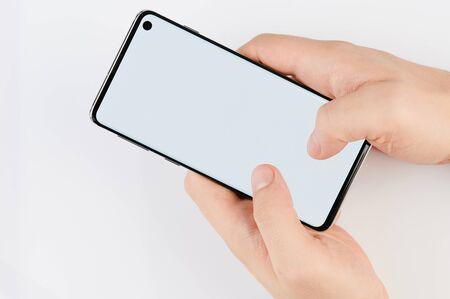 Foto de Blank smartphone screen in hand isolated on white background - Imagen libre de derechos