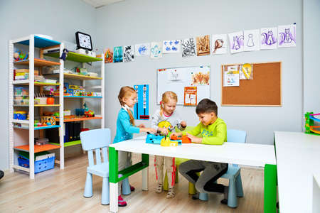 Photo pour Russia, Moscow, 01.01.2019, two girls and a boy in kindergarten are sitting at a table and playing toys - image libre de droit