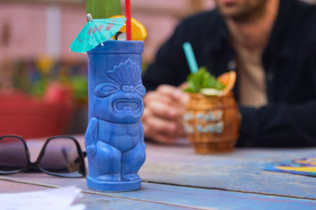 Photo pour Tropical cocktail with orange in blue tiki style glass on wooden background - image libre de droit