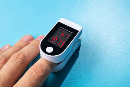 Photo for White new pulse oximeter on a blue table. measuring blood pressure and oxygen levels. pandemic examination Covid 19. the patient's hand. - Royalty Free Image
