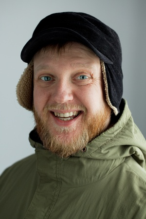 Cheerful young man in a hat and amusing green jacket