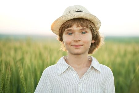 Happy boy in the hat among the wheat field on a summer evening