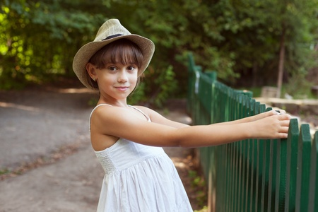 Pretty girl in the hat next to a fence
