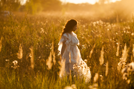 Girl walks through the meadow at sunset