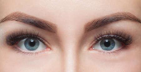 Foto de Eyelash removal procedure close up. Beautiful Woman with long lashes in a beauty salon. Look at the camera. - Imagen libre de derechos