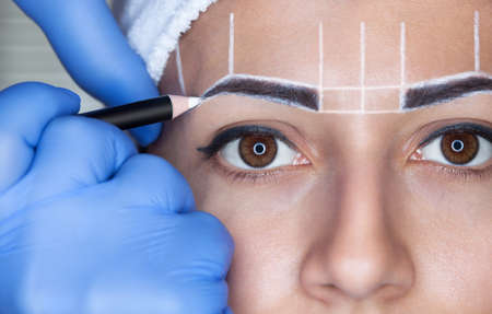 Photo pour Permanent make-up for eyebrows of beautiful woman with thick brows in beauty salon. Closeup beautician doing  tattooing eyebrow. - image libre de droit