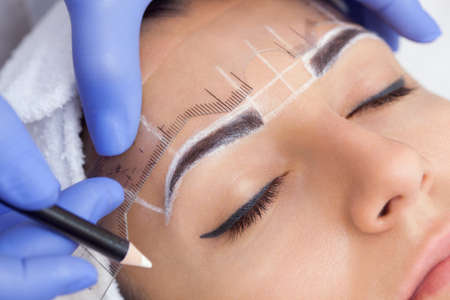 Photo for Permanent make-up for eyebrows of beautiful woman with thick brows in beauty salon. Closeup beautician doing  tattooing eyebrow. - Royalty Free Image