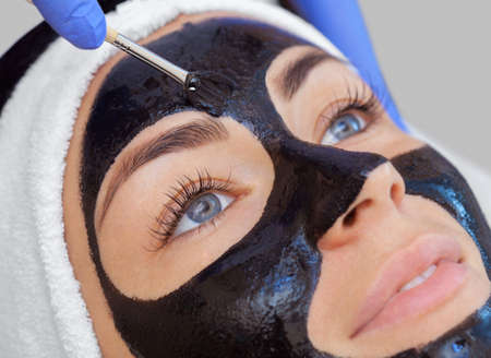 Foto de The procedure for applying a black mask to the face of a beautiful woman. Spa treatments and care of the cats in the beauty salon. - Imagen libre de derechos