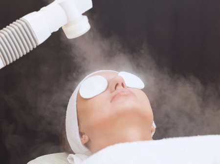 Photo pour The procedure of steaming the skin of the face of a young woman before cleaning the skin in a cosmetology salon. - image libre de droit